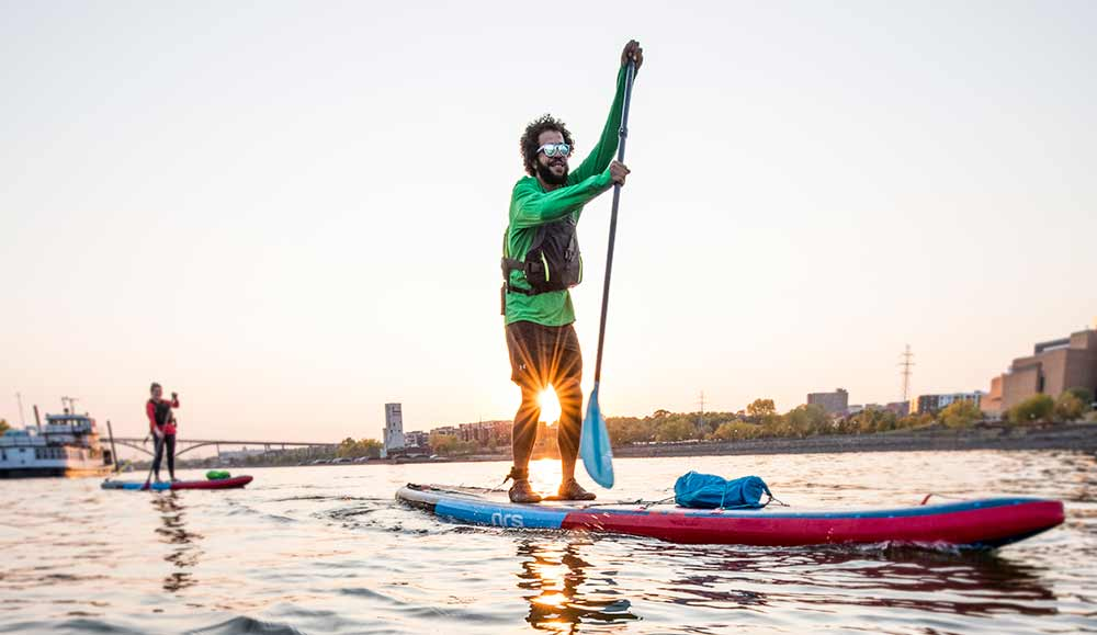 Stand up paddleboarding with city skyline in background.